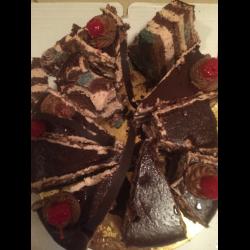 В форму насыпем обжаренные орешки, натёртый на тёрке с крупными отверстиями шоколод и нальём часть крема.